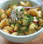 Skål med färsk potatissallad, helt nygjord så att strån av gräslök fastnar på sleven.