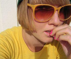 Clara klädd i gul t-shirt och gula solglasögon med plastbågar i gult. Ger 70-talskänsla.