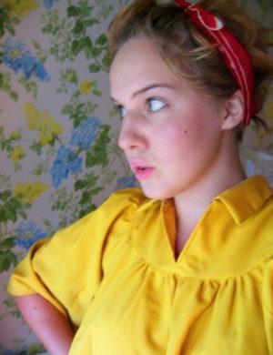Clara i gul blus tittar ut genom ett fönster.