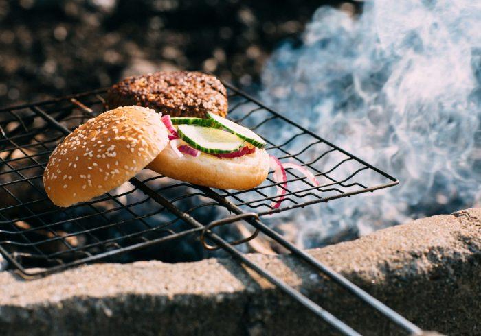 Rykande nygrillad vegetarisk burgare på grillgaller med eld och rök under.
