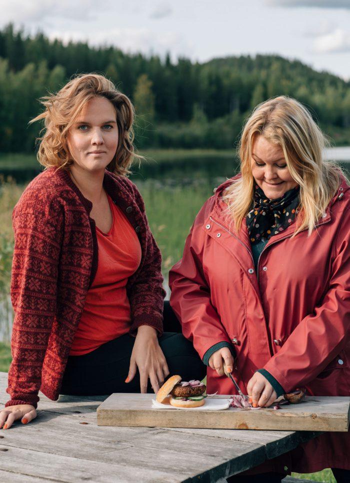 Clara och Erica ute i friska luften tidig höst, Erica har dukat upp vegburgare på skärbräda och skär lök.