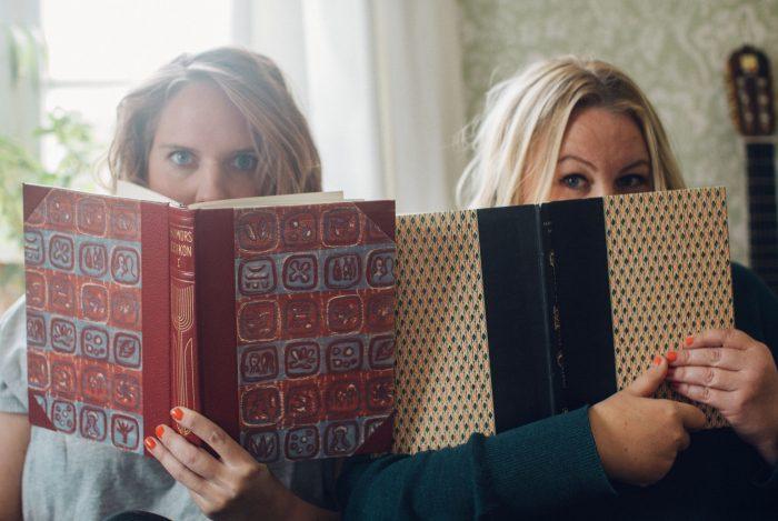 Clara och Erica sitter med näsorna djupt försjunkna i varsin bok. Ur En Underbar Pod.