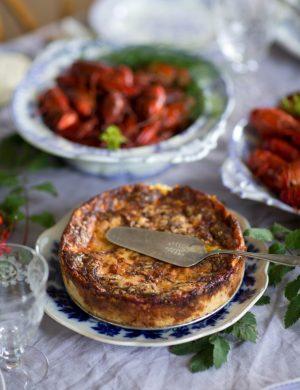 Rund härlig ostpaj i en gyllene färg, dukad intill skål med kräftor.