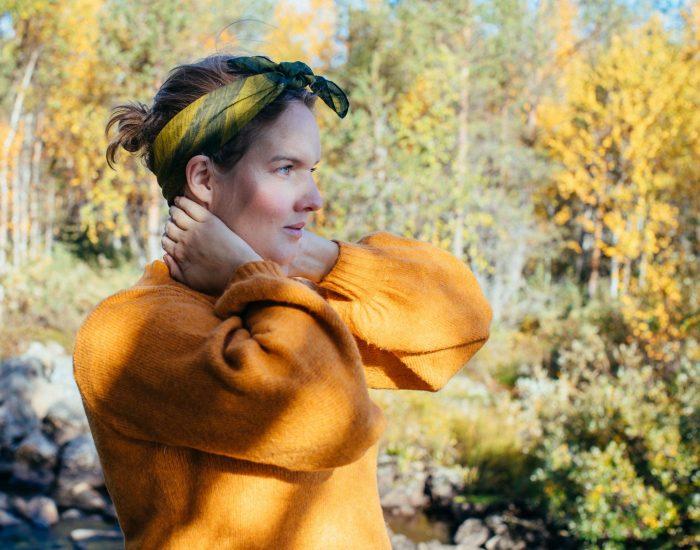 Clara klädd i gul stickad tröja tittar i profil i skogslandskap.