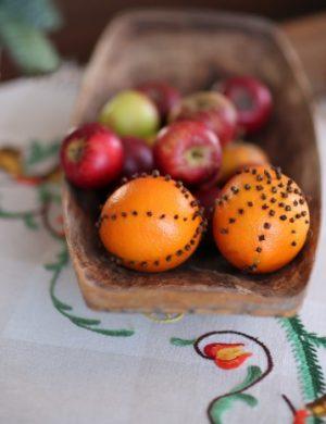 Gammeldags trätråg med juläpplen och apelsiner dekorerade med kryddnejlikor.
