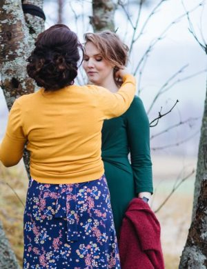 Annakarin och Clara i Miss Clarity-klänningar, Annakarin i gul kofta med rygg mot kameran rättar till Claras frisyr.