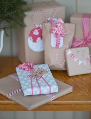 Julklappar inslagna i brunt papper varvat med ljusa pastellfärgade papper