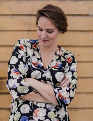 Clara i stormönstrad Miss Clarity-klänning, står med uppsatt hår mot gul trähusfasad.