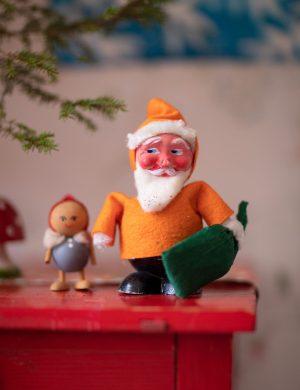 gul glad tomte står på bord i barnkammaren och sneglar mot en gran.