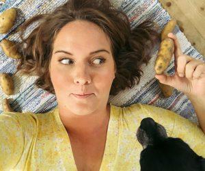 Clara håller i potatis i handen och tittar på den.
